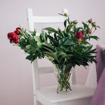 Blumenstrauß von roten pfingstrosen in einem vase auf dem weißen stuhl, heiratsdekoration