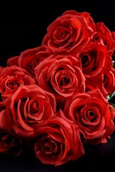 Blumenstrauß von roten rosen auf schwarzem hintergrund