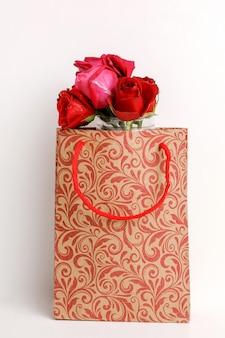 Blumenstrauß von roten rosen und von geschenkbox auf weißem hintergrund.