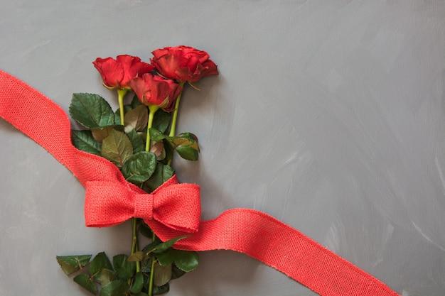 Blumenstrauß von roten rosen und von rotem band auf grau