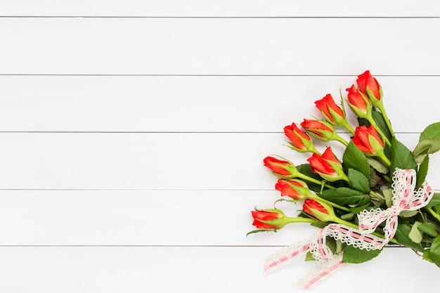 Blumenstrauß von roten rosen verziert mit spitze auf weißem hölzernem hintergrund. draufsicht, raum kopieren