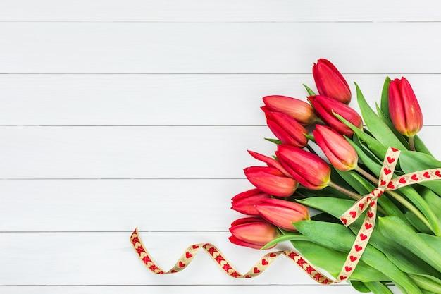 Blumenstrauß von roten tulpen auf weißem hölzernem hintergrund. draufsicht, raum kopieren. valentinstag, geburtstagskonzept.