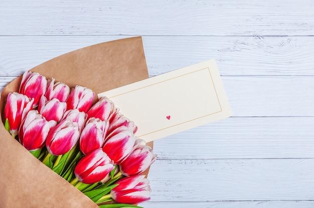 Blumenstrauß von roten tulpen für den tag der feiertagsfrauen und den valentinstag auf dem hintergrund von hölzernen brettern.