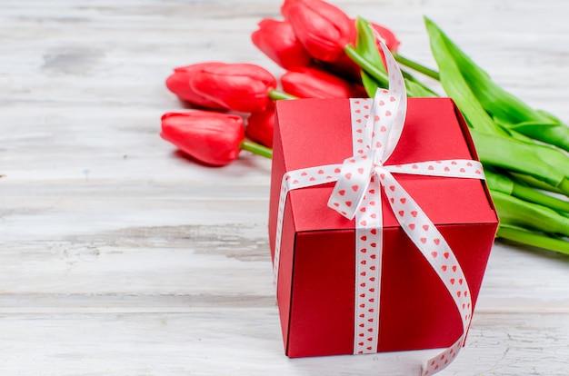 Blumenstrauß von roten tulpen und von geschenk des frühlinges