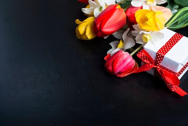 Blumenstrauß von roten tulpen, von narzissen und von geschenk auf dem schwarzen