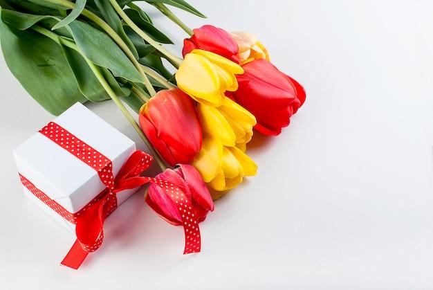 Blumenstrauß von roten tulpen, von narzissen und von geschenk auf dem weißen hintergrund