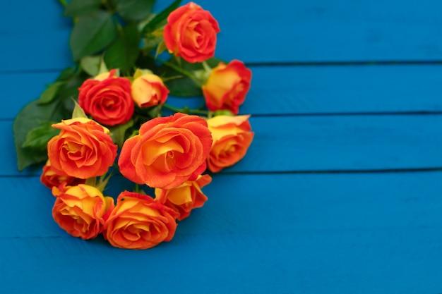 Blumenstrauß von schönen orange rosen auf blauem hintergrund