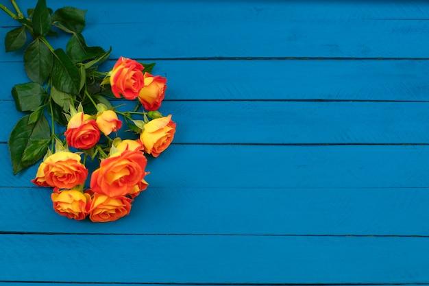 Blumenstrauß von schönen orange rosen auf blauem hölzernem hintergrund