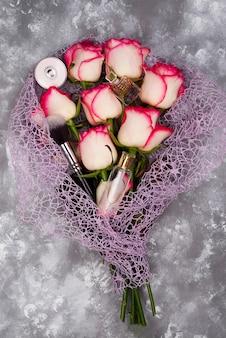 Blumenstrauß von schönen rosen mit kosmetik auf grauem beton