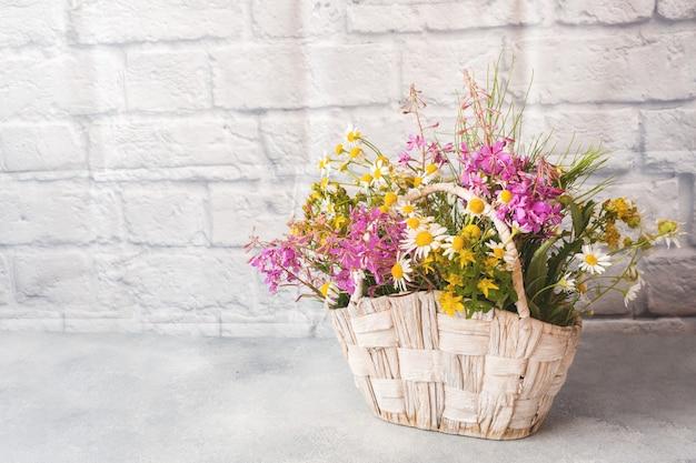 Blumenstrauß von schönen wildflowers in einem korb auf einer grauen oberfläche mit kopienraum.