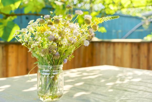 Blumenstrauß von sommerwildblumen und kräutern im glas auf tisch auf terrasse, sonniger tag, rustikaler stil