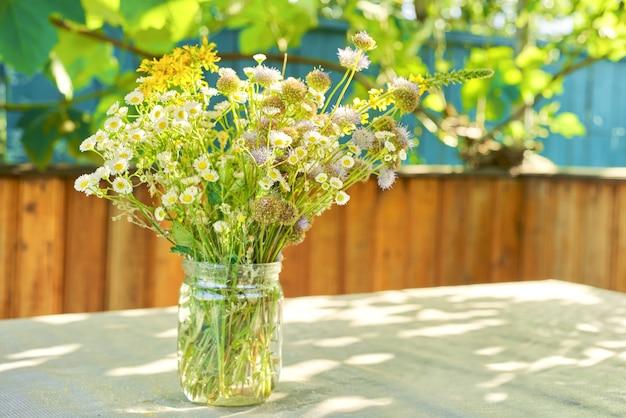 Blumenstrauß von sommerwildblumen und kräutern im glas auf tisch auf terrasse