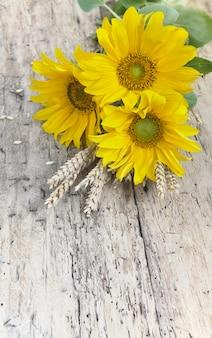Blumenstrauß von sonnenblumen mit trockenem weizen auf einer rustikalen tabelle