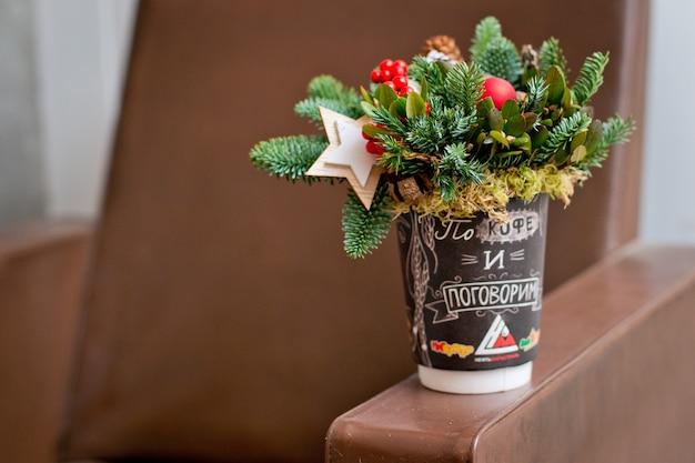 Blumenstrauß von tannenzweigen in einer roten schale und in weihnachten spielt auf einem konkreten hintergrund.