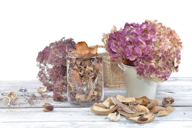 Blumenstrauß von trockenen blumen und von trockenblumengesteck in einem glasgefäß auf einer weißen tabelle