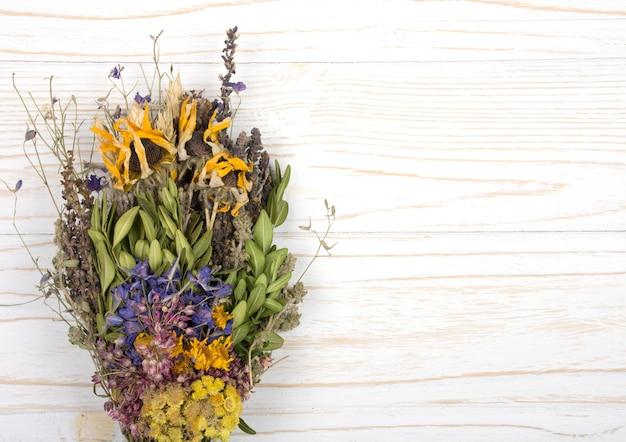 Blumenstrauß von trockenen kräutern auf einem weißen hölzernen hintergrund