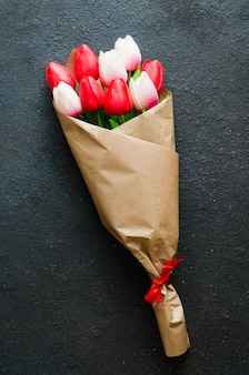 Blumenstrauß von tulpen auf dunklem hintergrund für den tag des valentines, der frauen oder der mutter.