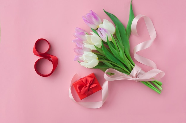 Blumenstrauß von tulpen auf einem rosa pastellhintergrund.