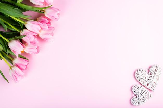 Blumenstrauß von tulpen und herzen auf rosa hintergrund. draufsicht, flacher laienstil.