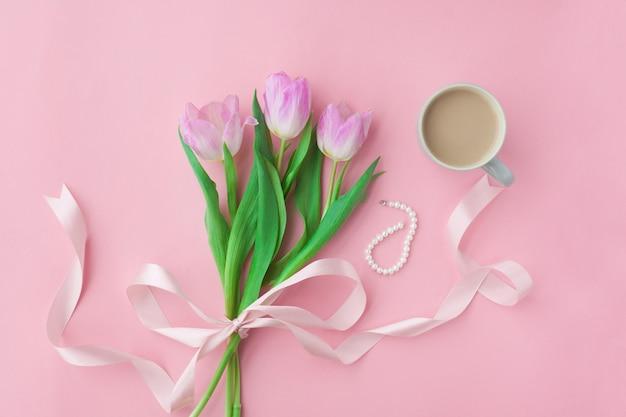 Blumenstrauß von tulpen und von kaffeetasse auf einem rosa pastellhintergrund.