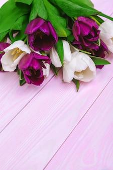 Blumenstrauß von tulpenblumen auf rosa hölzernem hintergrund mit kopienraum