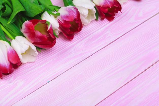 Blumenstrauß von tulpenblumen auf rosa hölzernem hintergrund