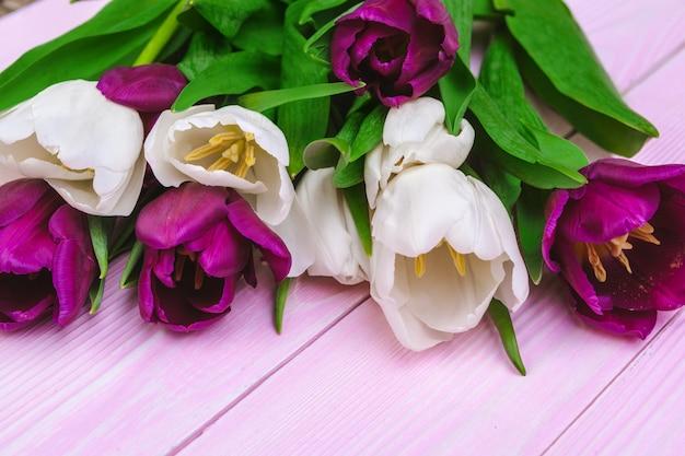 Blumenstrauß von tulpenblumen auf rosa holz mit copyspace