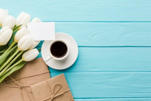 Blumenstrauß von tulpenblumen mit kaffee und packpapier