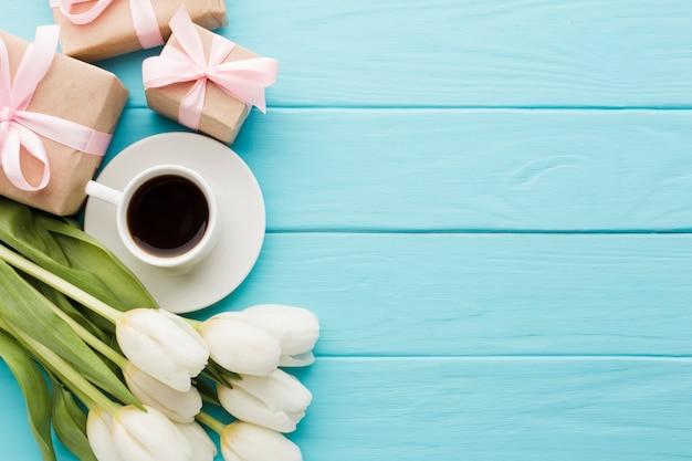 Blumenstrauß von tulpenblumen mit morgenkaffee und geschenkboxen