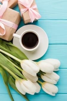 Blumenstrauß von tulpenblumen mit tasse kaffee und geschenken