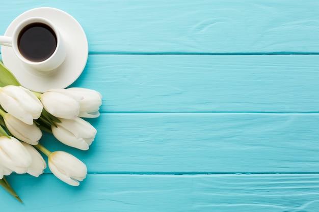Blumenstrauß von tulpenblumen mit tasse kaffee