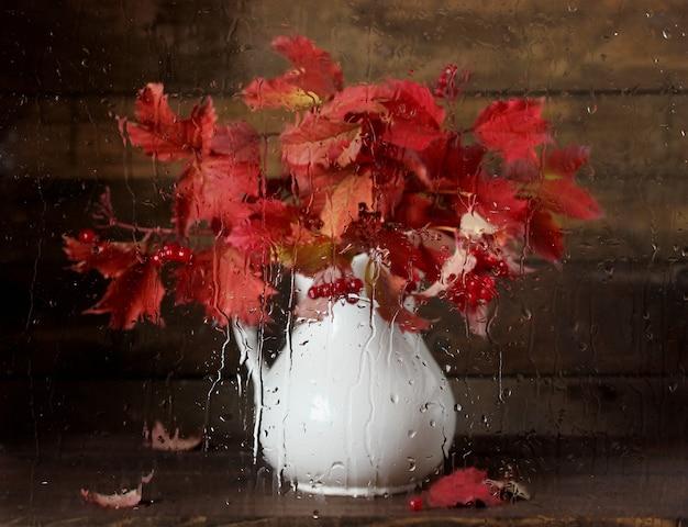 Blumenstrauß von viburnum mit roten blättern und beeren hinter einem nassen fenster mit wassertropfen. herbstliches stillleben. regen.