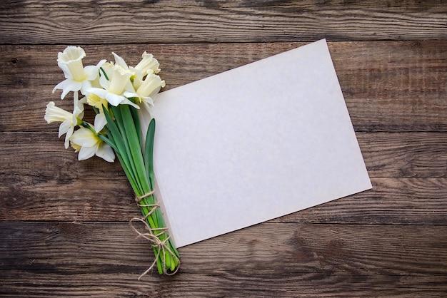 Blumenstrauß von weiß mit gelben narzissen und blatt papier für das schreiben auf hölzernen hintergrund