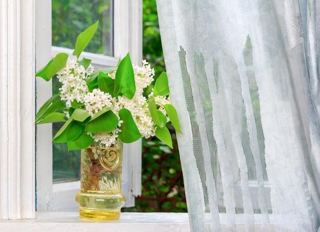 Blumenstrauß von weißen lila blumen auf einem weißen fensterbrett in einem dorfhaus