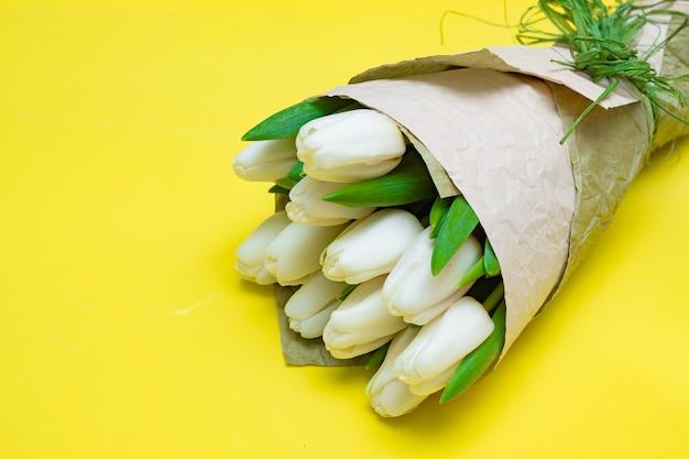 Blumenstrauß von weißen tulpen auf einer gelben tabelle. flach liegen.