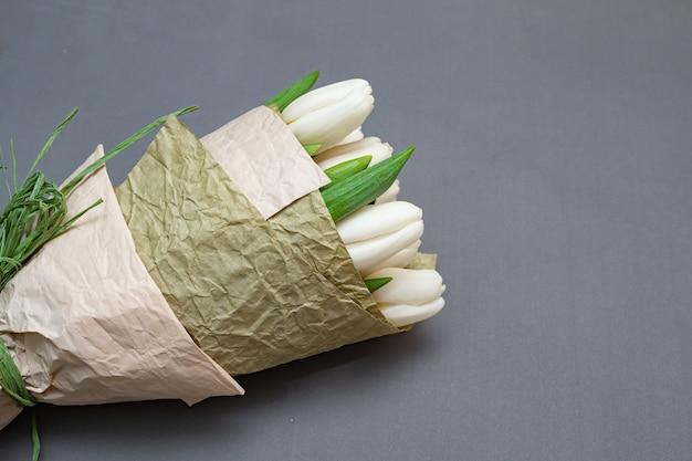 Blumenstrauß von weißen tulpen auf einer grauen tabelle. flay lat.