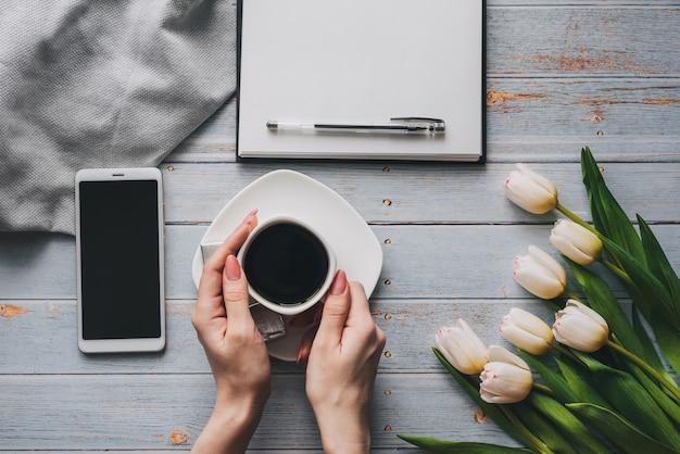 Blumenstrauß von weißen tulpen mit einem tasse kaffee in den händen der frauen, in einem smartphone und in einem leeren notizbuch für text
