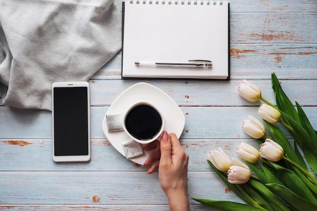 Blumenstrauß von weißen tulpen mit einem tasse kaffee in den händen der frauen, in einem smartphone und in einem leeren notizbuch