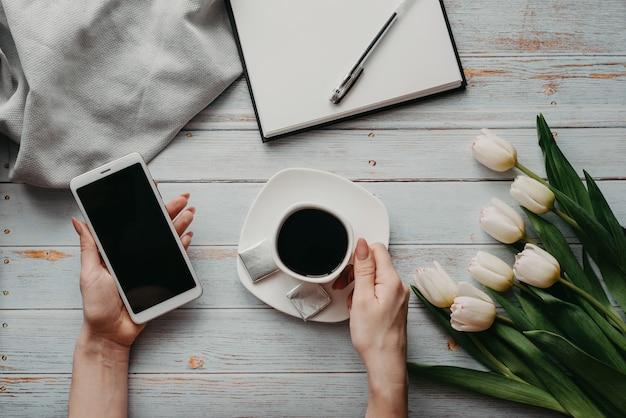 Blumenstrauß von weißen tulpen mit einem tasse kaffee und einem smartphone in der hand der frauen und in einem leeren notizbuch auf einem holztisch