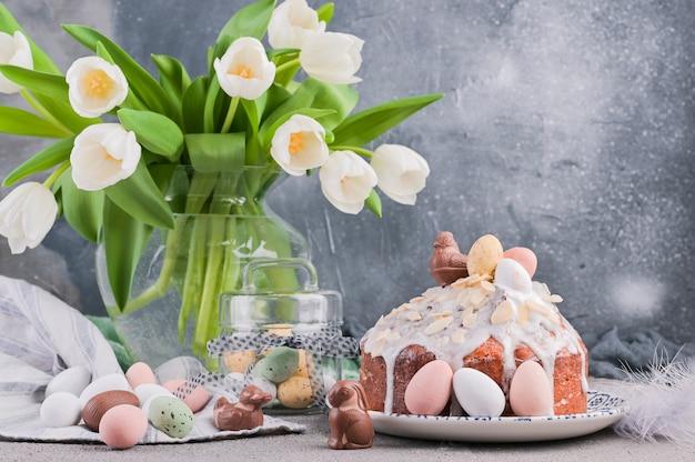 Blumenstrauß von weißen tulpen und von ostern-kleinem kuchen auf einem grauen hintergrund.