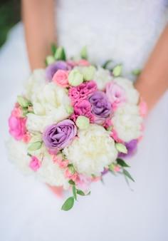 Blumenstrauß von weißen, violetten und rosa blumen in den armen der frau