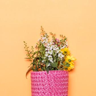 Blumenstrauß von wilden blumen in der rosa tasche