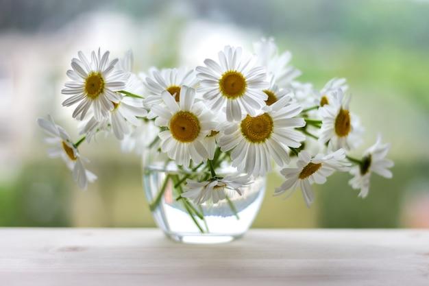 Blumenstrauß von wilden gänseblümchen in einem kleinen glasvase auf holztisch und unscharfem hintergrund.