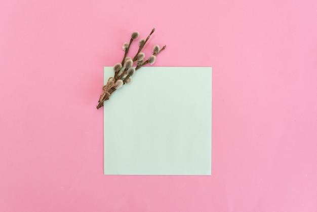 Blumenstrauß von zarten rosa rosen mit einer leeren grußkarte und einem umschlag auf weißem rustikalem hölzernem hintergrund