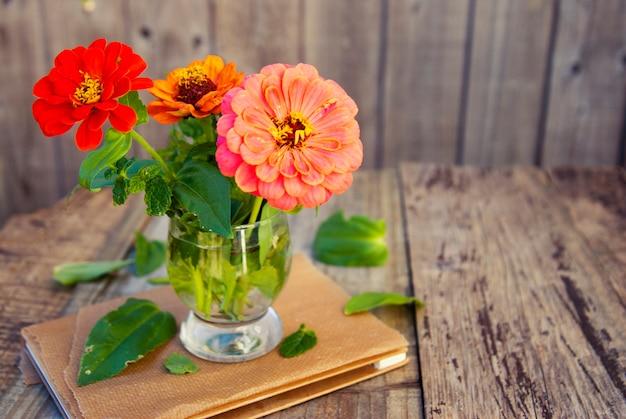 Blumenstrauß von zinniablumen auf rustikalem holztisch. copyspace.