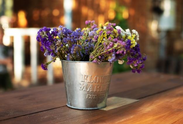 Blumenstraußblumen in der weinlesevase auf holztisch im garten. gemütliche einrichtung des innenhofs