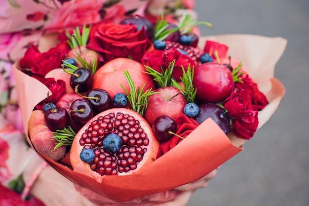 Blumenstraußblumen und frische zitrusfrüchte in grobem papier in händen eingewickelt