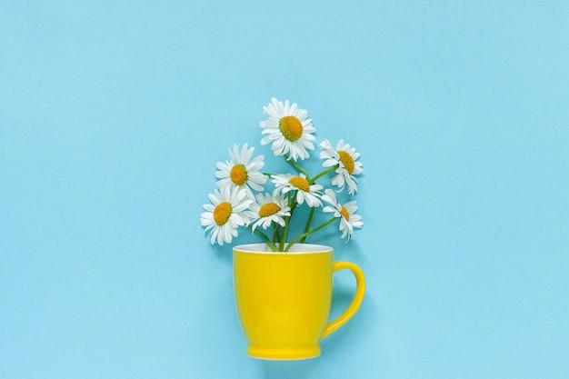 Blumenstraußkamillengänseblümchen blüht im gelben becher auf blauem pastellfarbpapierhintergrund