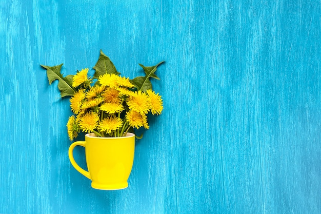Blumenstraußlöwenzahn taraxacum blüht im gelben becher auf hölzernem blauem hintergrund
