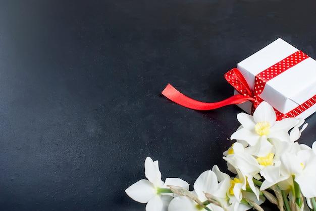 Blumenstraußnarzissen und -geschenk auf dem schwarzen hintergrund